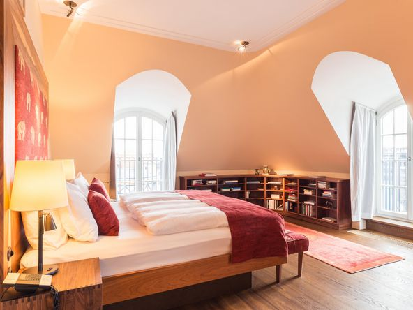 Suite furnished in warm colours with two large windows in the background and a large bed.