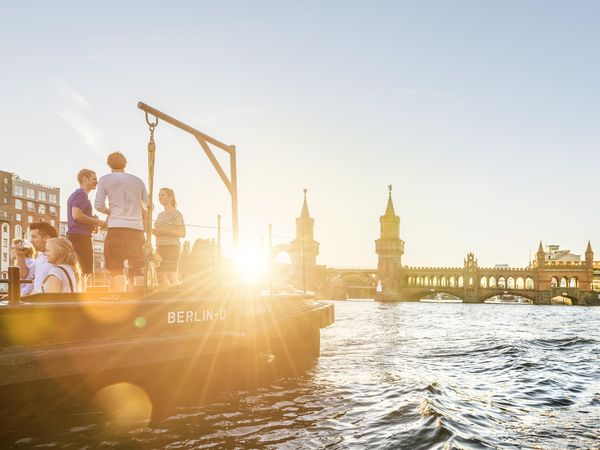 [Translate to Deutsch:] A boat with several young people lies in the sunset in front of the Oberbaum bridge.