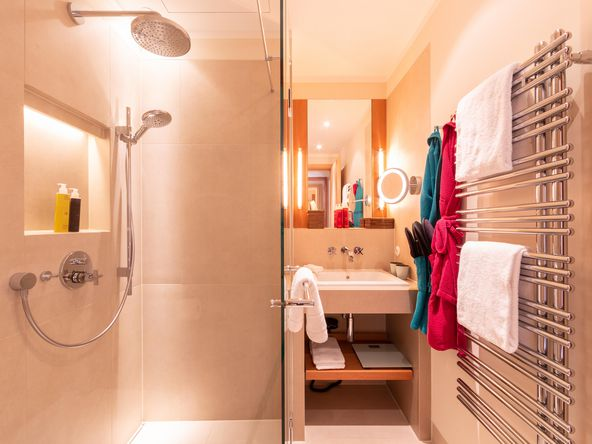 Towel heating in bathroom with shower and washbasin with mirror in OraniaBerlin