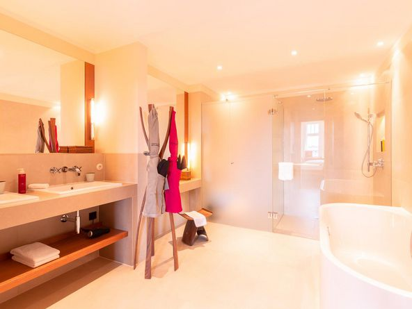 Interior view of the brightly furnished bathroom with standing shower, bath possibility and two bathrobes