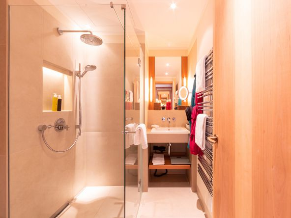 Interior view of the bathroom with rainshower and washbasin and suspended towels