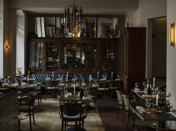 [Translate to Deutsch:] View into a restaurant with many small tables, vintage furniture, in the background there is a large wooden cupboard to see