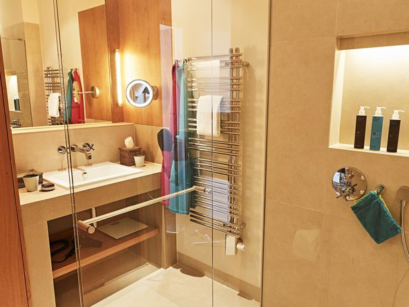 Transparent glass pane of the shower with washbasin, towels and washing utensils
